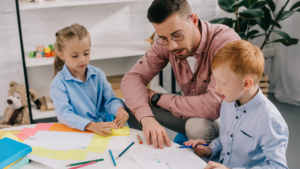 A teacher works with two early-years pupils